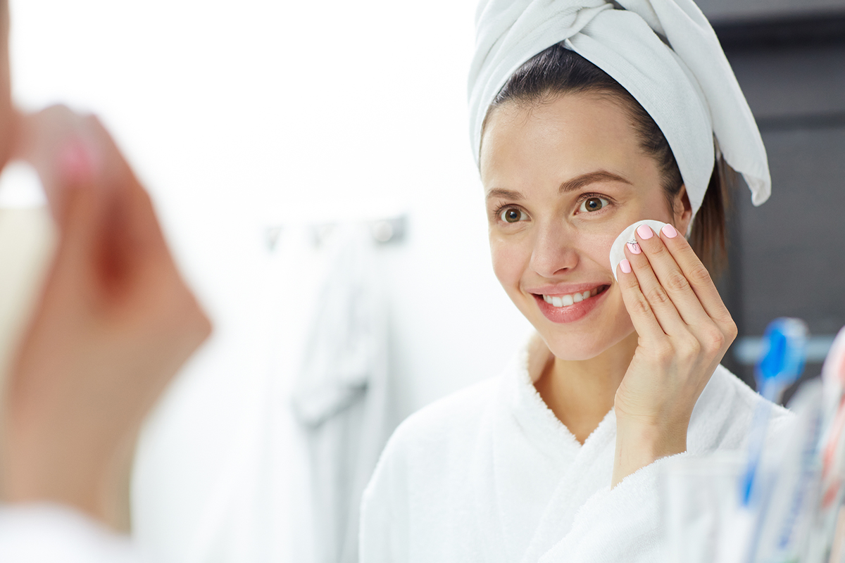 Pretty girl removing makeup in front of mirror