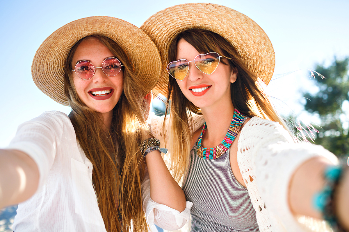 Two pretty best friends girls making selfie on beach, light and bright summer colors, boho chic clothes hats and sunglasses, trendy jewelry and natural make up, positive friendship vibes.