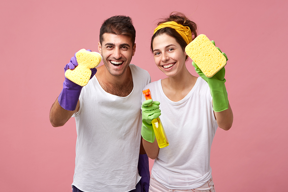Housekeeping, cleanliness, hygiene and domestic work concept. Happy Caucasian young family in protective rubber gloves using detergent and rags while tidying up in the kitchen together on weekend
