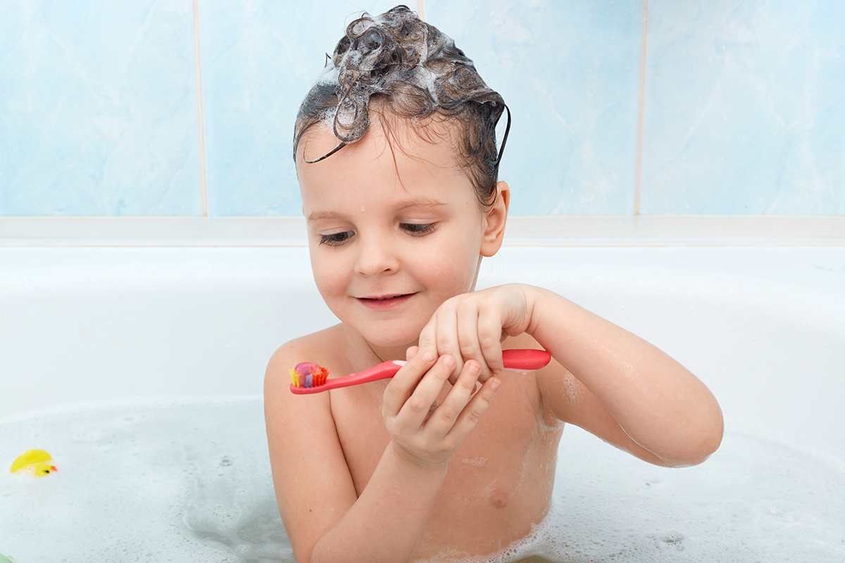 Shot of little child brushing her teeth while taking bath, charming wet lady holds red tooth brush, has foam on her hair, having fun while washing, glad to clean teeth by herself, water procedures.